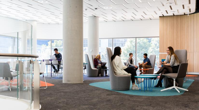Students sit on lounges and stools around tables overlooking Alumni Green