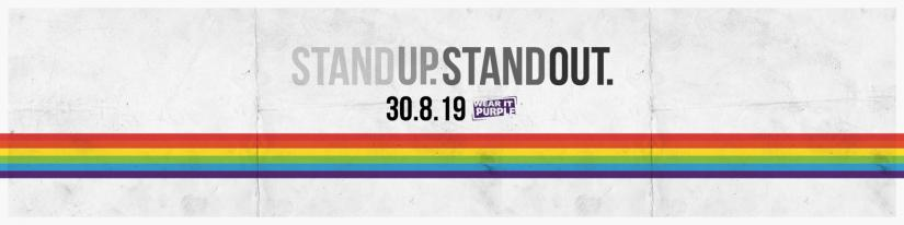 A rainbow (in the style of the Pride flag) runs along the length of the image. Text on image: Stand up. Stand out. 30-08-19 Wear it Purple.