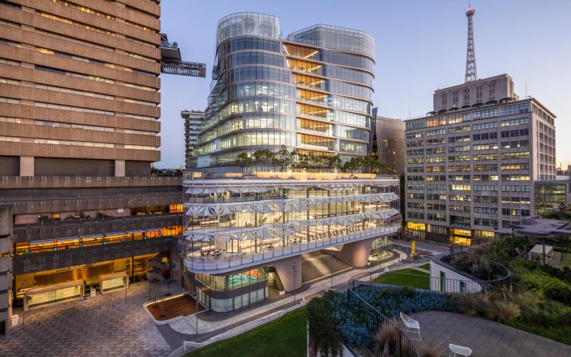 UTS Central at twilight shining beside the Brutalist Tower building.