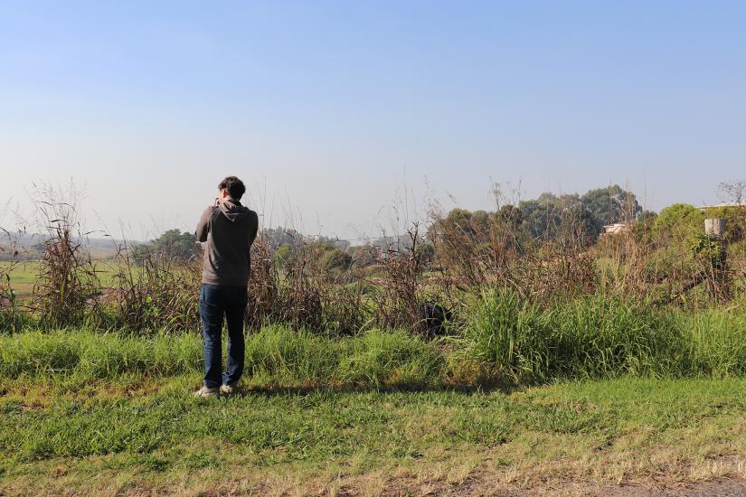 The back of a student taking a photo, standing in a grassy landscape.