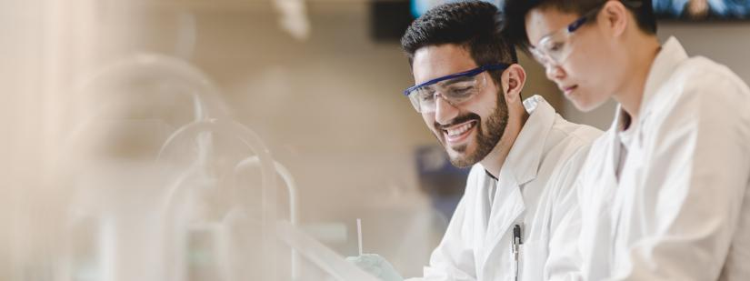 Two scientists leaning over a lab bench