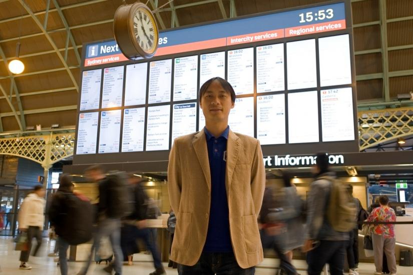 A man stands in front of a train schedule