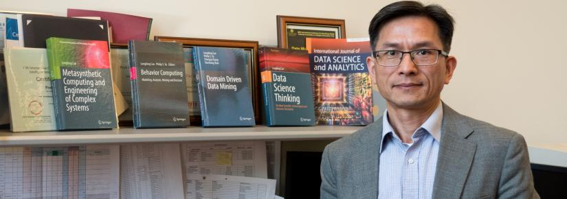Professor Longbing Cao standing in front of his desk next to data science books.