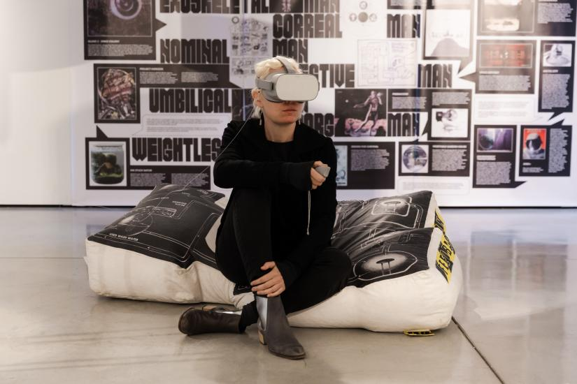 A person seated on a large bean bag, wearing a virtual reality headset. Behind them, the wall is covered in text and images.
