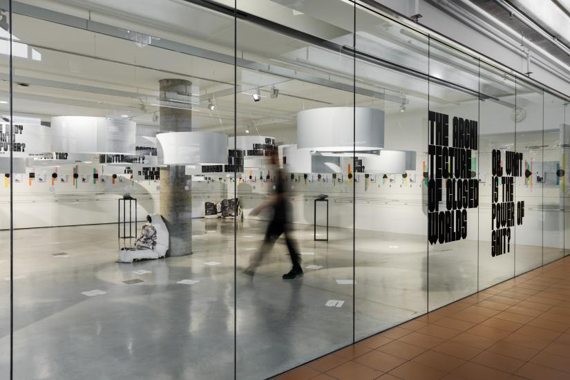 Looking into the exhibition through the glass wall of the UTS Gallery. There is black text on the glass, and a blurred figure is walking through the space. Inside the gallery is predominantly white and grey, with a timeline marked out on the white walls and white cylinders hanging from the ceiling.