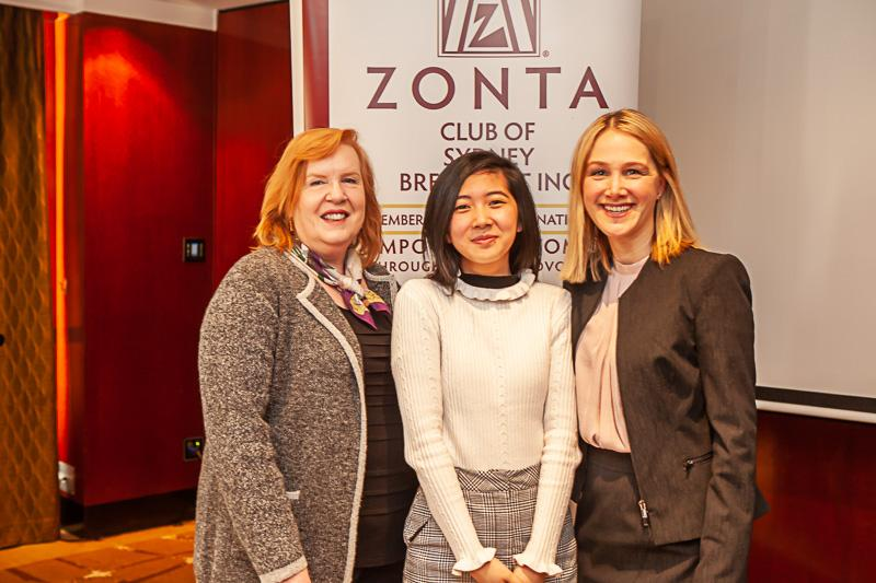 Three women in front of Zonta banner