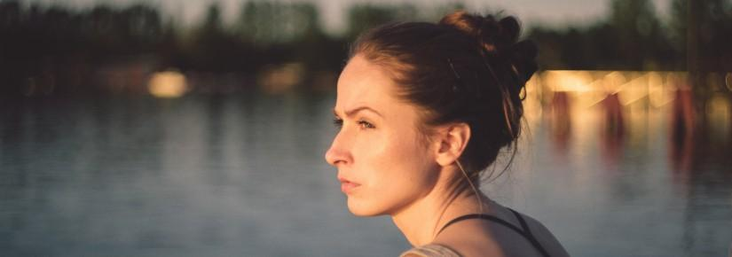 A woman stares into the distance, there is water behind her
