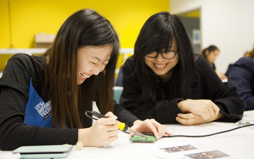 Two female engineering students sit at a desk laughing.