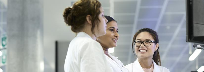 Three women in lab coats looking at a computer screen.