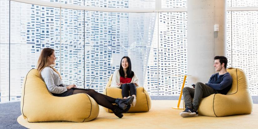 Three students sit on bean bag chairs in UTS Central.
