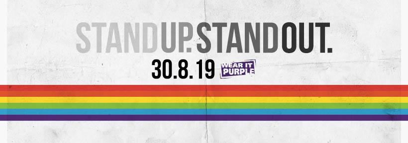 Wear it Purple Day 2019. A rainbow in the style of the Pride flag runs across the image. Text in image: Stand up. Stand out. 30-08-19 Wear it Purple