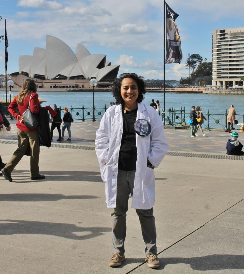 Woman in lab coat in front of Sydney Opera House