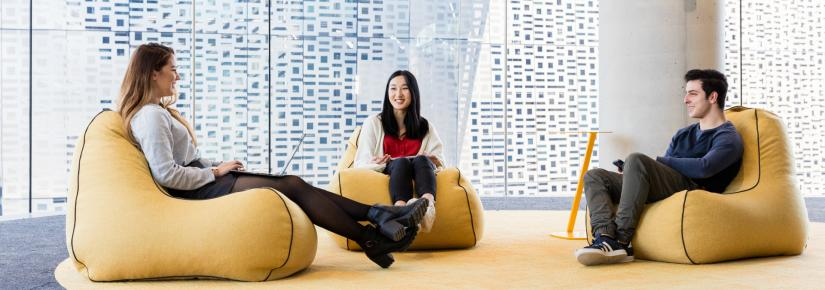Three UTS students sit on colourful bean bag chairs and talk at UTS Central.