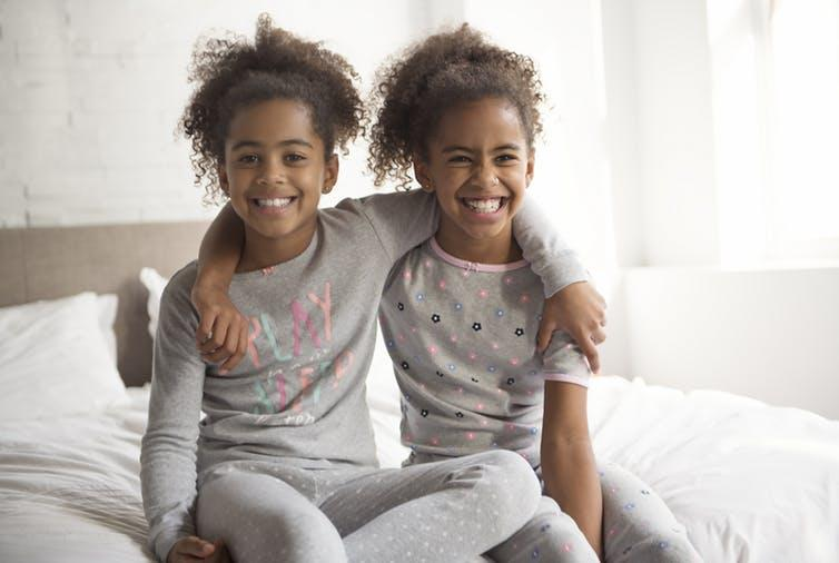 Image of two identical twin girls sitting on a bed with arms around each other