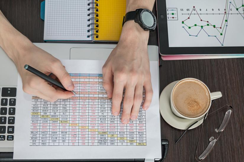closeup of hand writing on printed spreadsheet of numbers, at table with laptop and cup of coffee