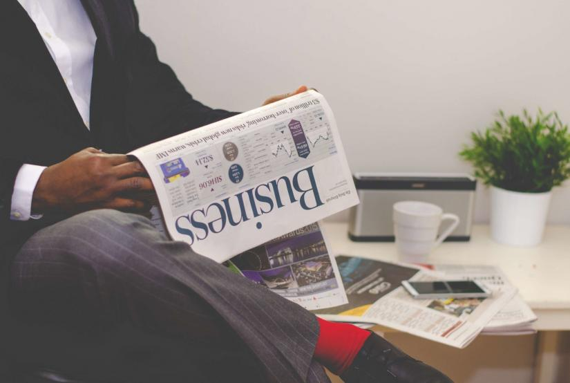 cropped shot of seated man reading Business section of newspaper