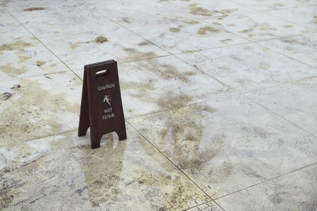 "Photo of wet tiled floor with ""Caution: Wet Floor"" sign"