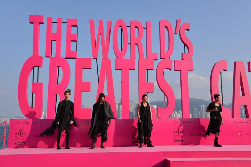Four models wearing black stand on a bright pink stage