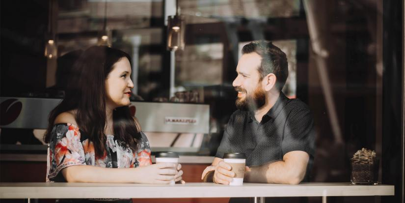 Two people smiling and chatting over coffee