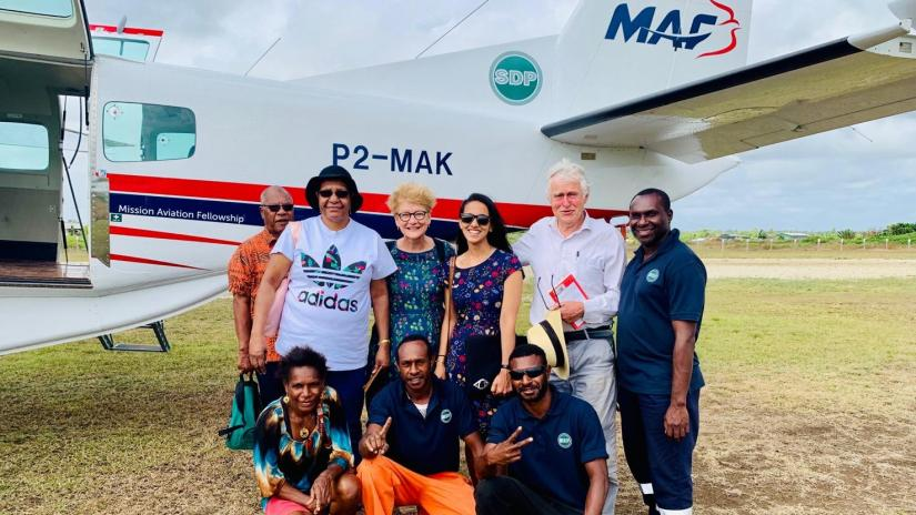 Bhanvi Kapoor Anand and colleagues in front of small plane in PNG