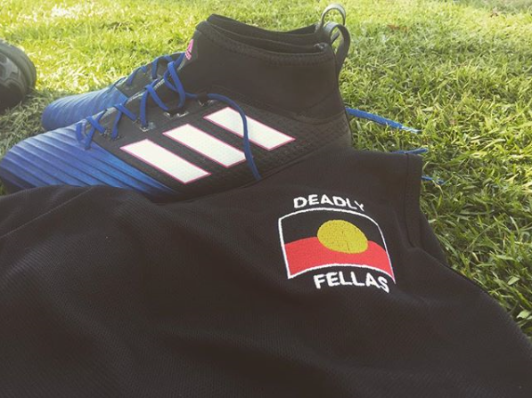 Image of football jersey and boots on grass