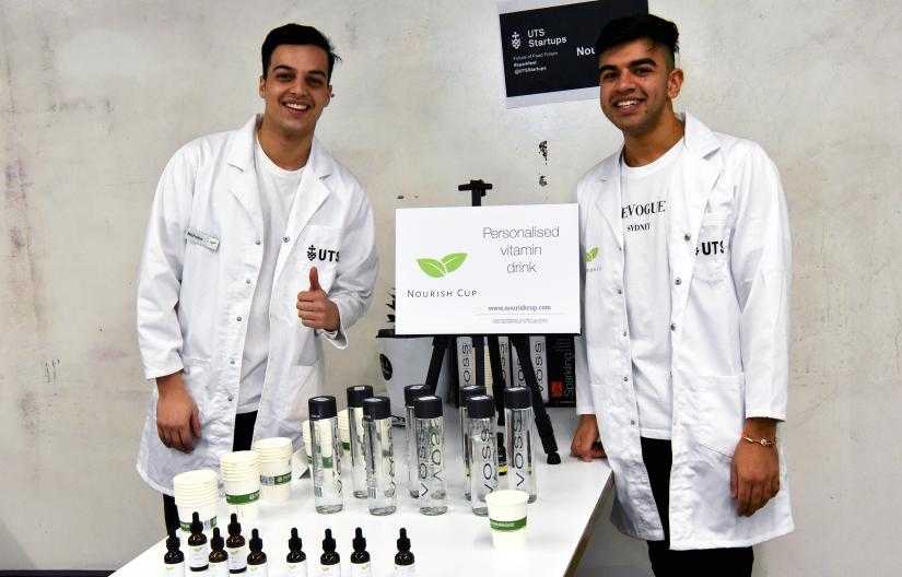 Two students from the UTS startup Nourish Cup beside a table with their products on display