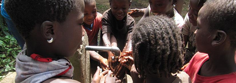 Children in Haiti wash their hands at a water spout during a cholera vaccination campaign.
