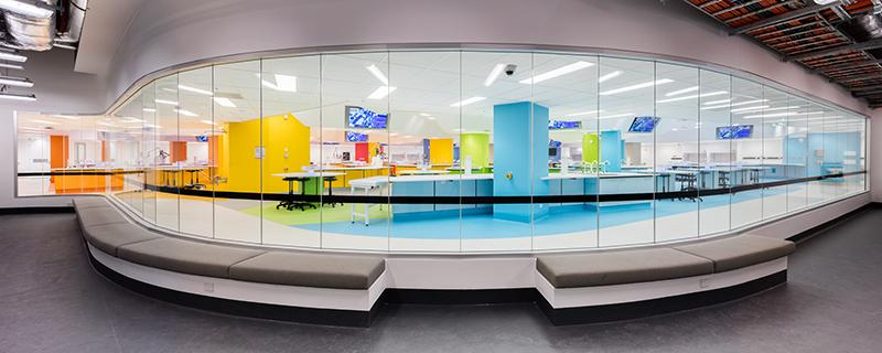 Looking through the observation glass into Hive Superlab, a multicoloured lab space with hexagonal benches and large data screens