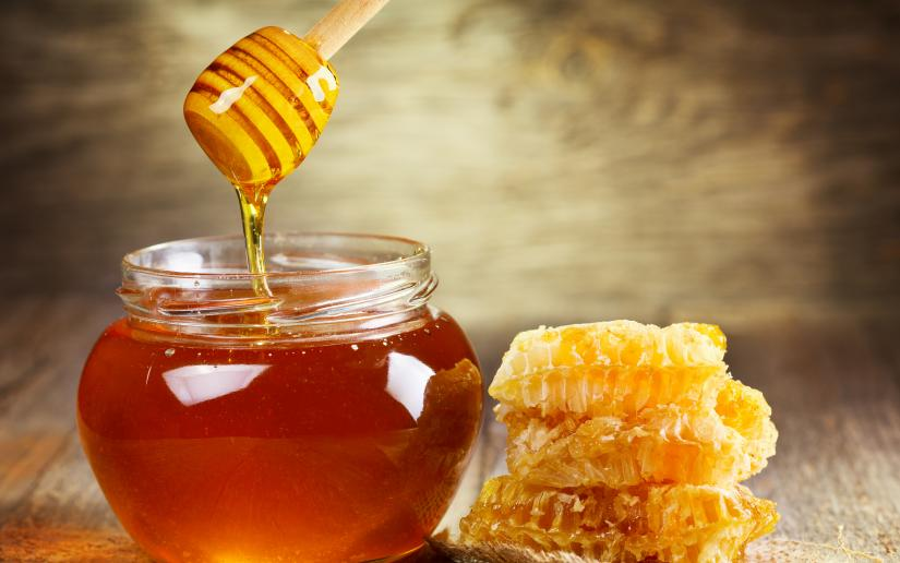 A spoon dripping with honey is held over a pot of honey next to a honeycomb.