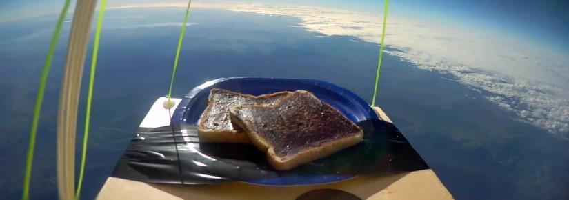 A fish-eye shot of vegemite toast on a blue plate and piece of wood. Below it is the earth.