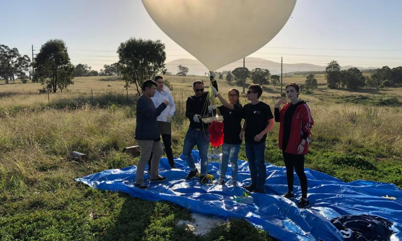 Six people standing on a blue tarp, holding the toast and a white weather balloon