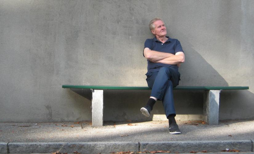 Stock image of a man sitting on a bench with arms folded looking into the distance