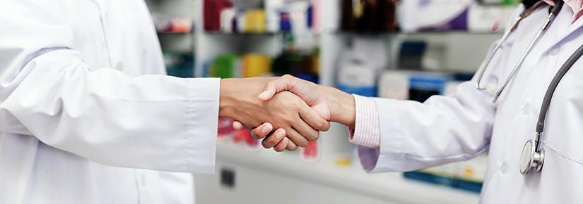 Stock picture of two people in lab coats shaking hands in a pharmacy, one identified as a doctor with a stethoscope around her neck.