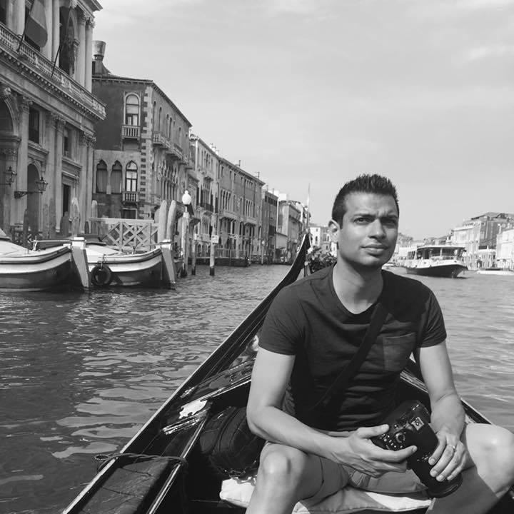 Akash Arora sitting in a canal boat in Venice - black and white