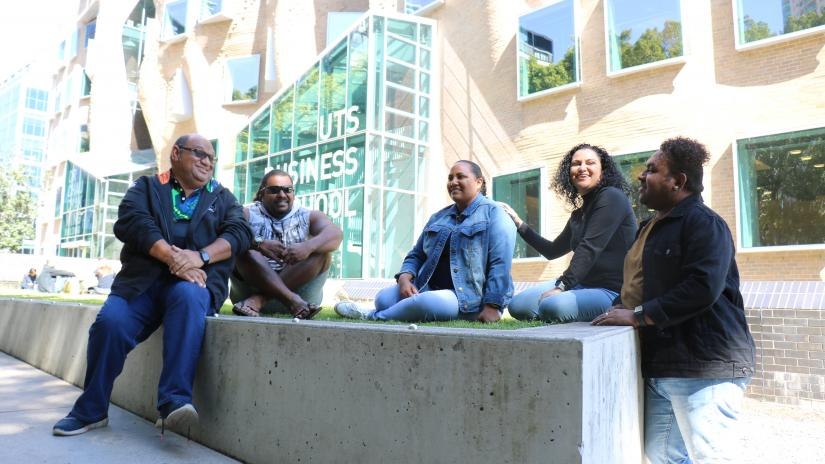 Yanetta Nadredre and her four family members sitting outside the UTS Business School