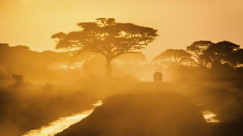 A jeep driving at sunset on a dusty road in a rural African landscape