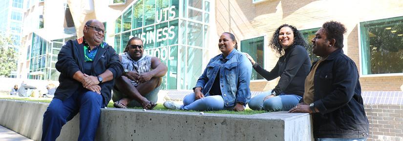 Five BBA students, David Abednego, Rodney Kiwat, Jasmine Bond, Yanetta Nadredre and Lyell Reuben sitting on the lawn outside the UTS Busines School