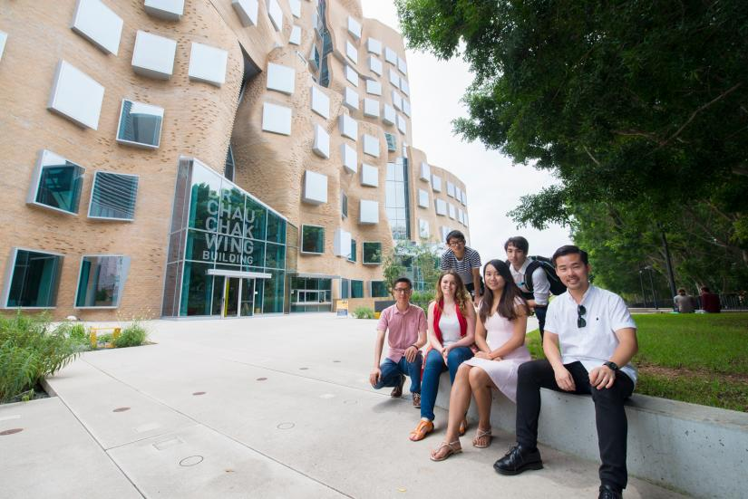 Dr Chau Chak Wing Scholars sitting on ledge in front of Building 8