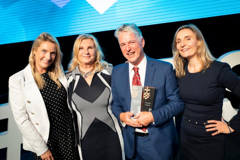 Martin Hill (holding his awards) with his daughter Virginia Phillips, wife Lisa Hill and daughter Sarah Hill smiling at the camera