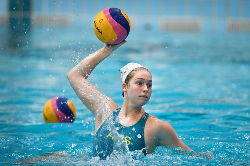 Alice Williams in the water throwing a water polo ball