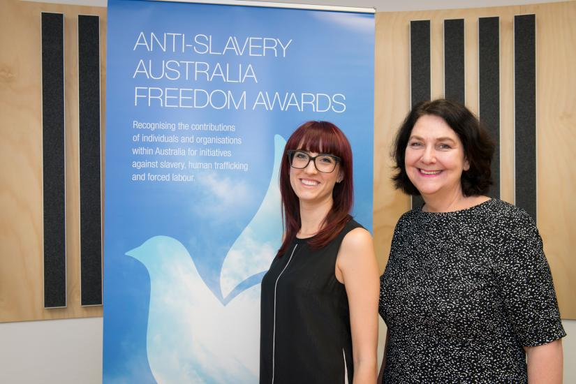 The Anti-Slavery team standing in front of the Freedom Awards pull up banner