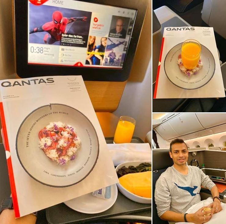 Image of Akash on board Qantas flight looking at Qantas magazine