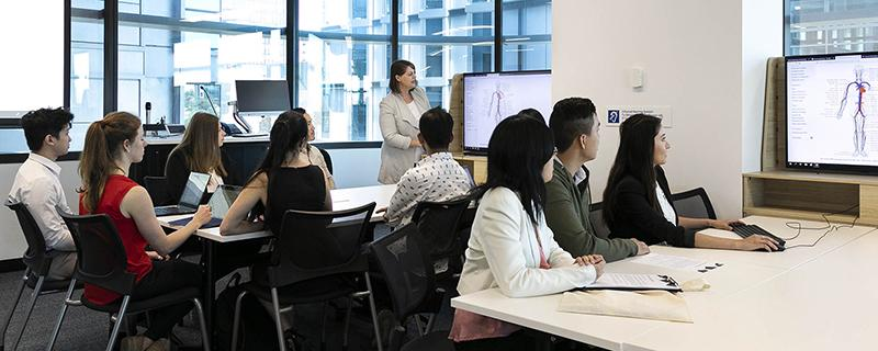 Groups of students work around tables with large screens at the ends while an instructor delivers information