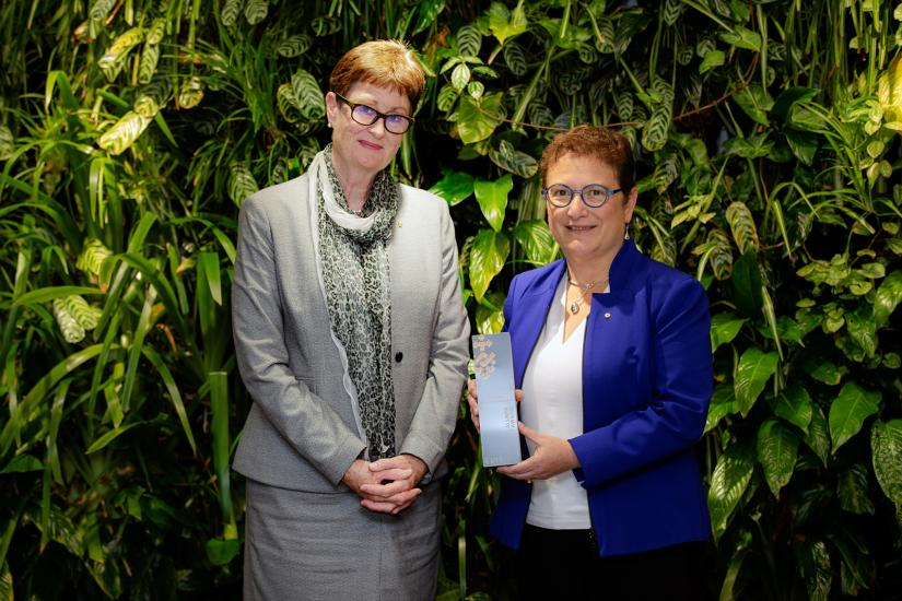 UTS Chancellor Catherine Livingstone with Professor Maria Kavallaris AM standing in front of a plant wall