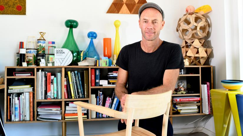 Adam Goodrum in his studio with his arm leaning on a library chair