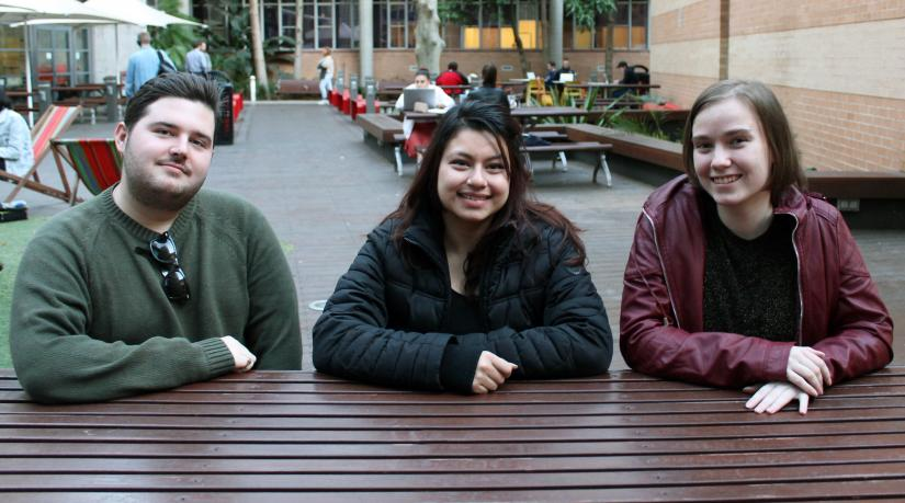 Oliver, Aarya and Remi-Rose sitting at a wooden table smiling at the camera