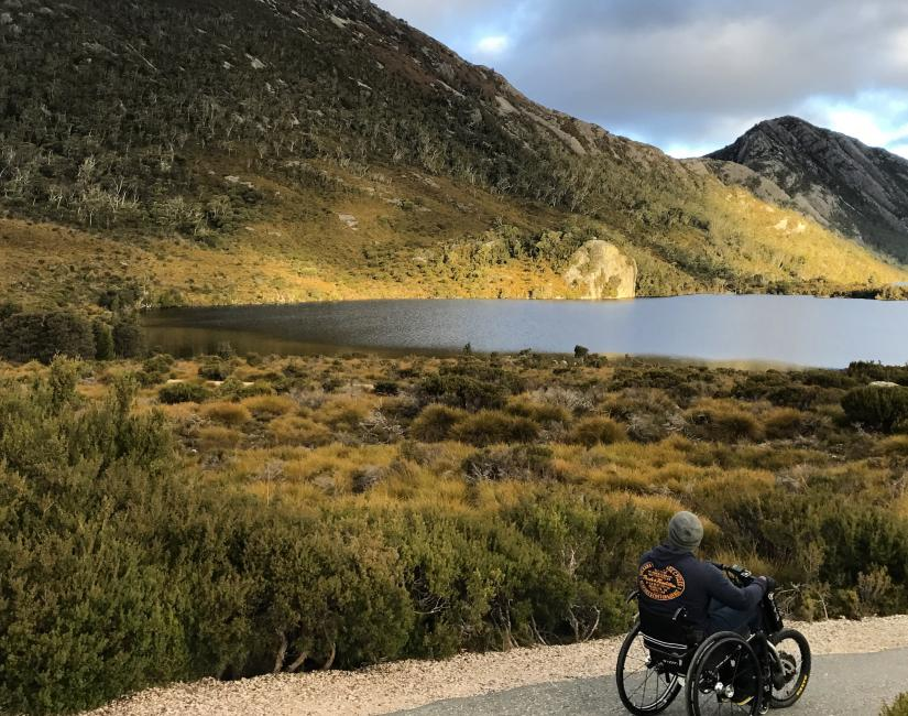 Alex in a wheelchair looking towards a mountain