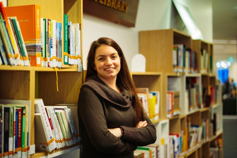 Brooke Ottley smiling at the camera whilst leaning against bookshelves in the library