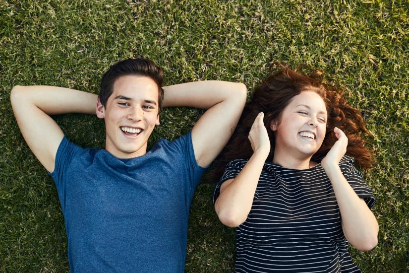 Two people lying on grass laughing