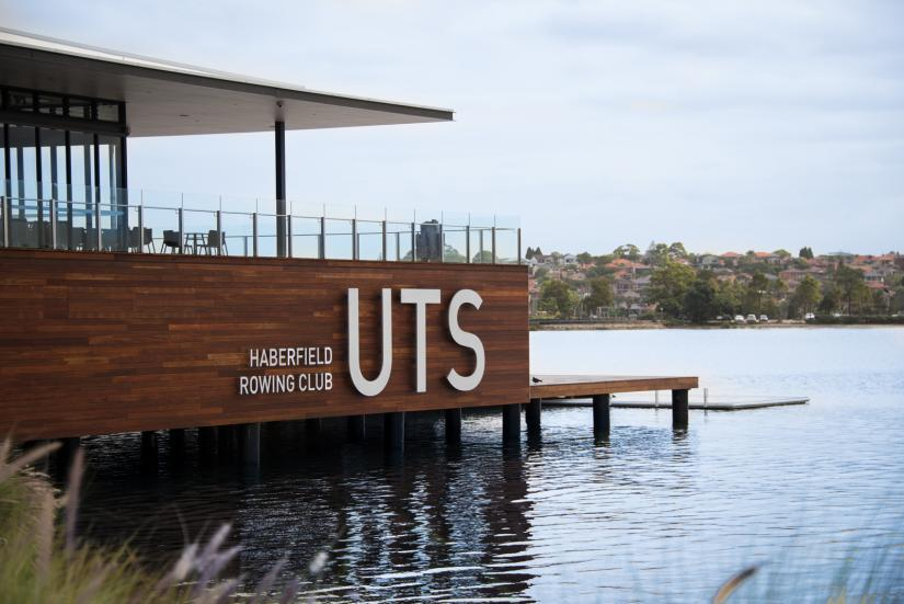 UTS Rowing Club with grass in the foreground and water around it